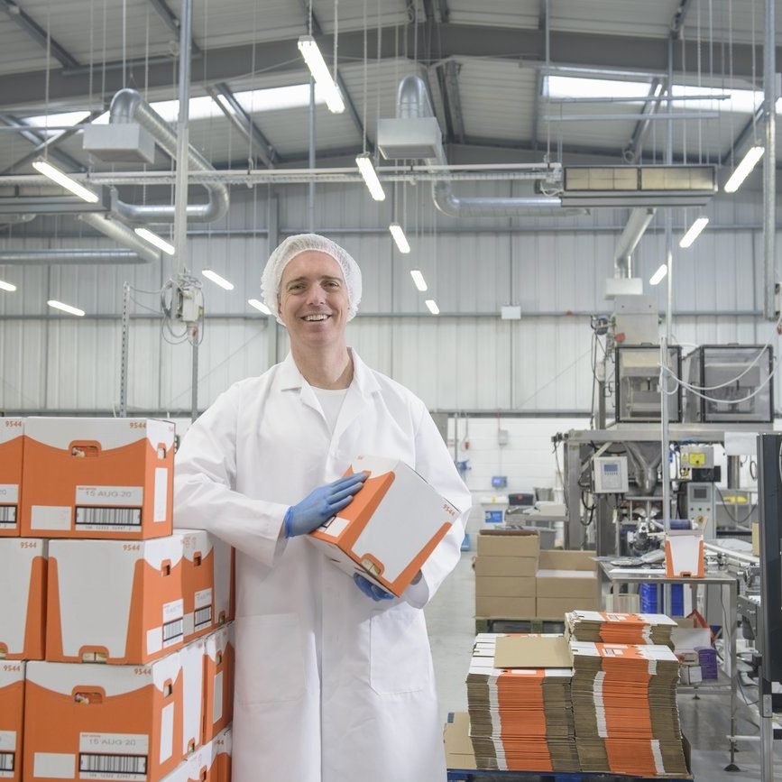 PAC factory staff in lab coat and hairnet holding package.